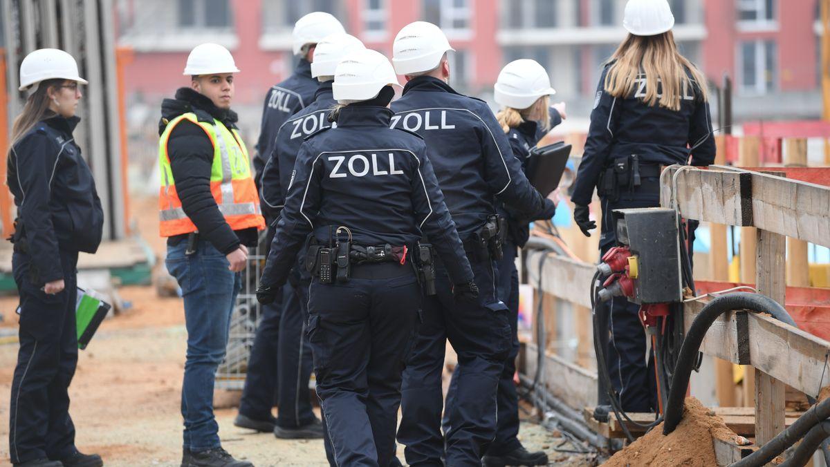 Beamte der Finanzkontrolle Schwarzarbeit gehen während eines Einsatzes über eine Großbaustelle (Symbolbild).