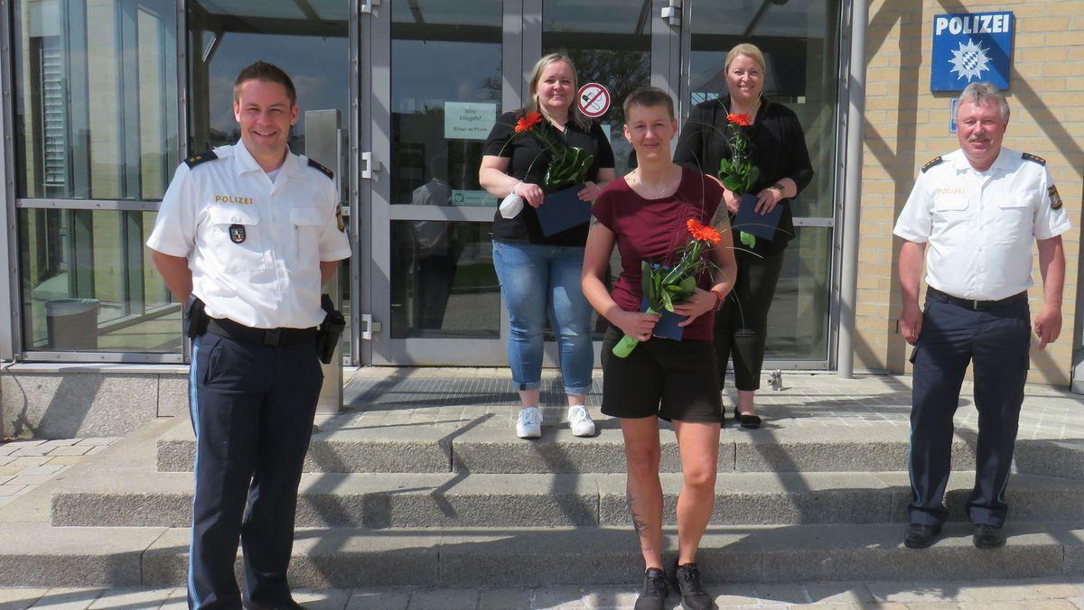 Die drei McDonald's-Mitarbeiterinnen und zwei Polizisten stehen vor einem Polizei-Gebäude.
