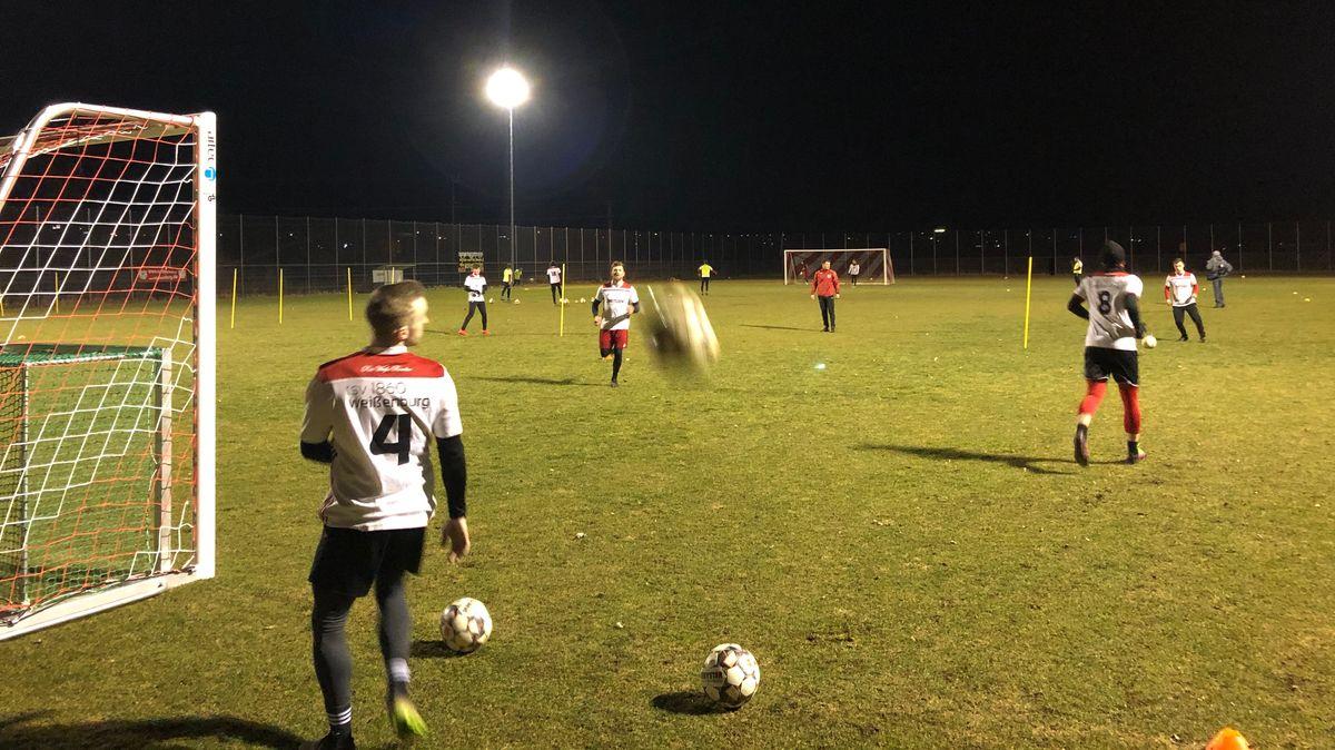 Fußballer trainieren auf einem Fußballplatz bei Flutlicht.