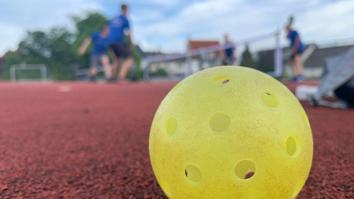 Ein gelber Ball mit Löchern liegt auf einem roten Hartplatz.