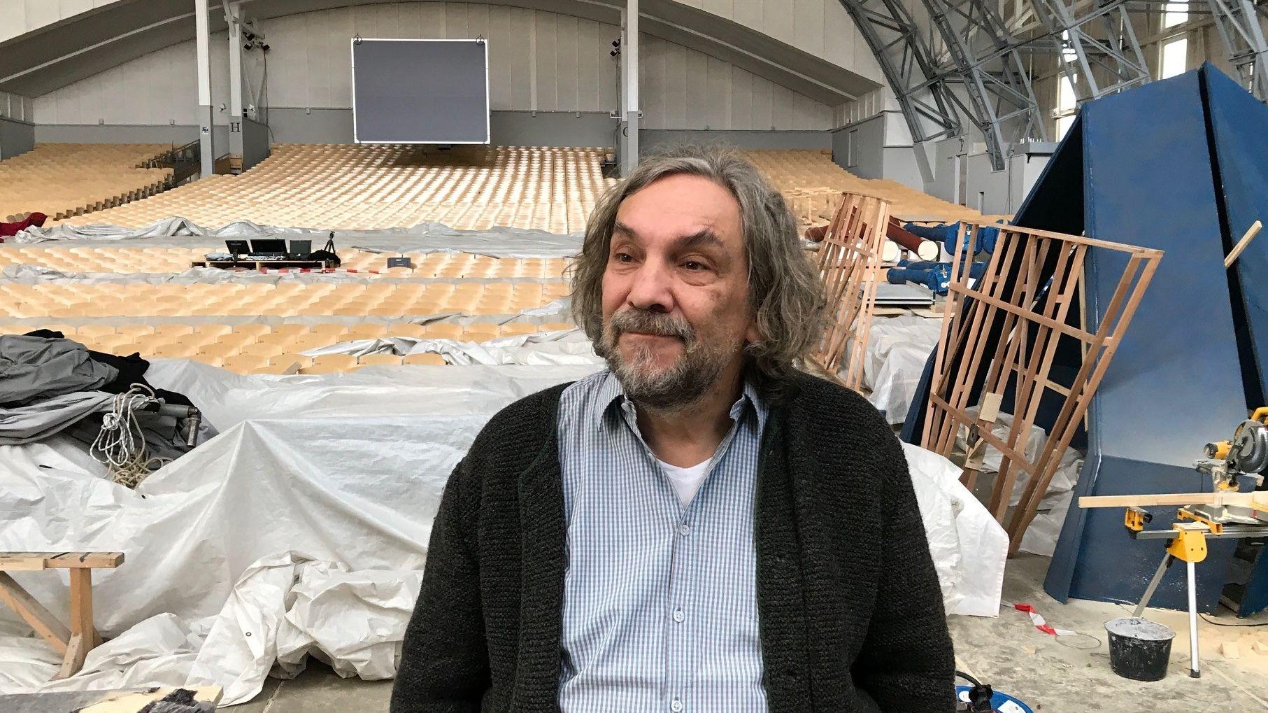 Spielleiter Christian Stückl sitzt in Hemd und Janker vor einem kreativen Bühnenchaos