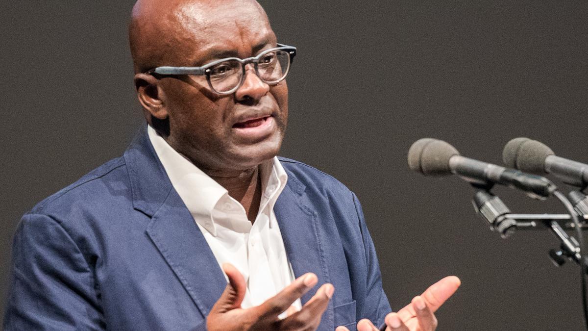 Politikwissenschaftler Achille Mbembe steht an einem Rednerpult mirt zwei Mikrofonen und spricht