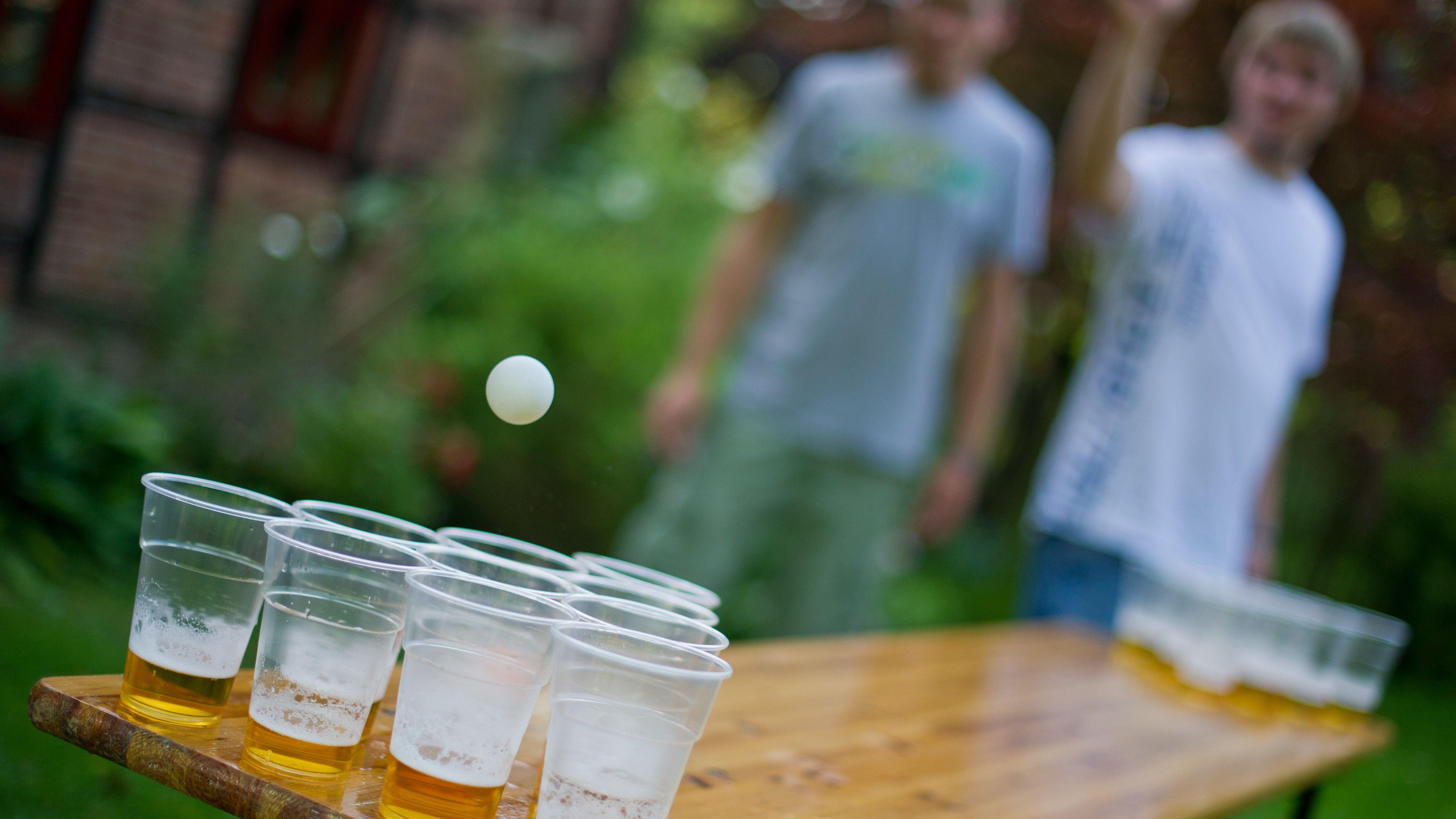 Zwei Personen stehen an einem Biertisch, auf dem mehrere Plastikbecher gefüllt mit Bier stehen.