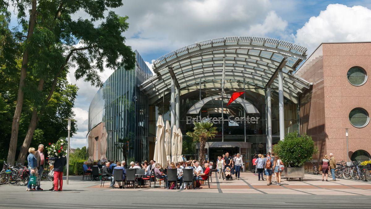 Außenansicht des Brücken-Centers in Ansbach. Davor sitzen Menschen auf Stühlen bzw. gehen zum Einkaufen.
