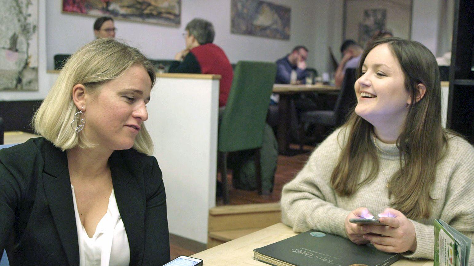 VdK-Präsidentin Verena Bentele und ihre Referentin Laura Bürzer sitzen sich in einem Restaurant gegenüber