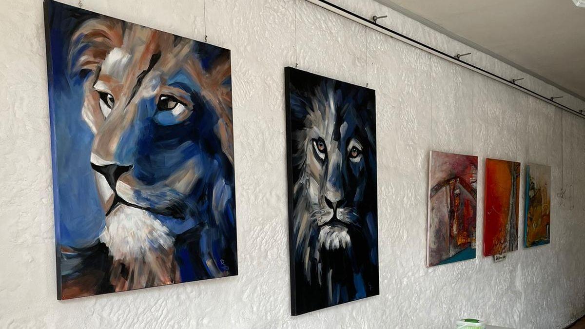 Löwen-Bilder hängen an einer weißen Wand.