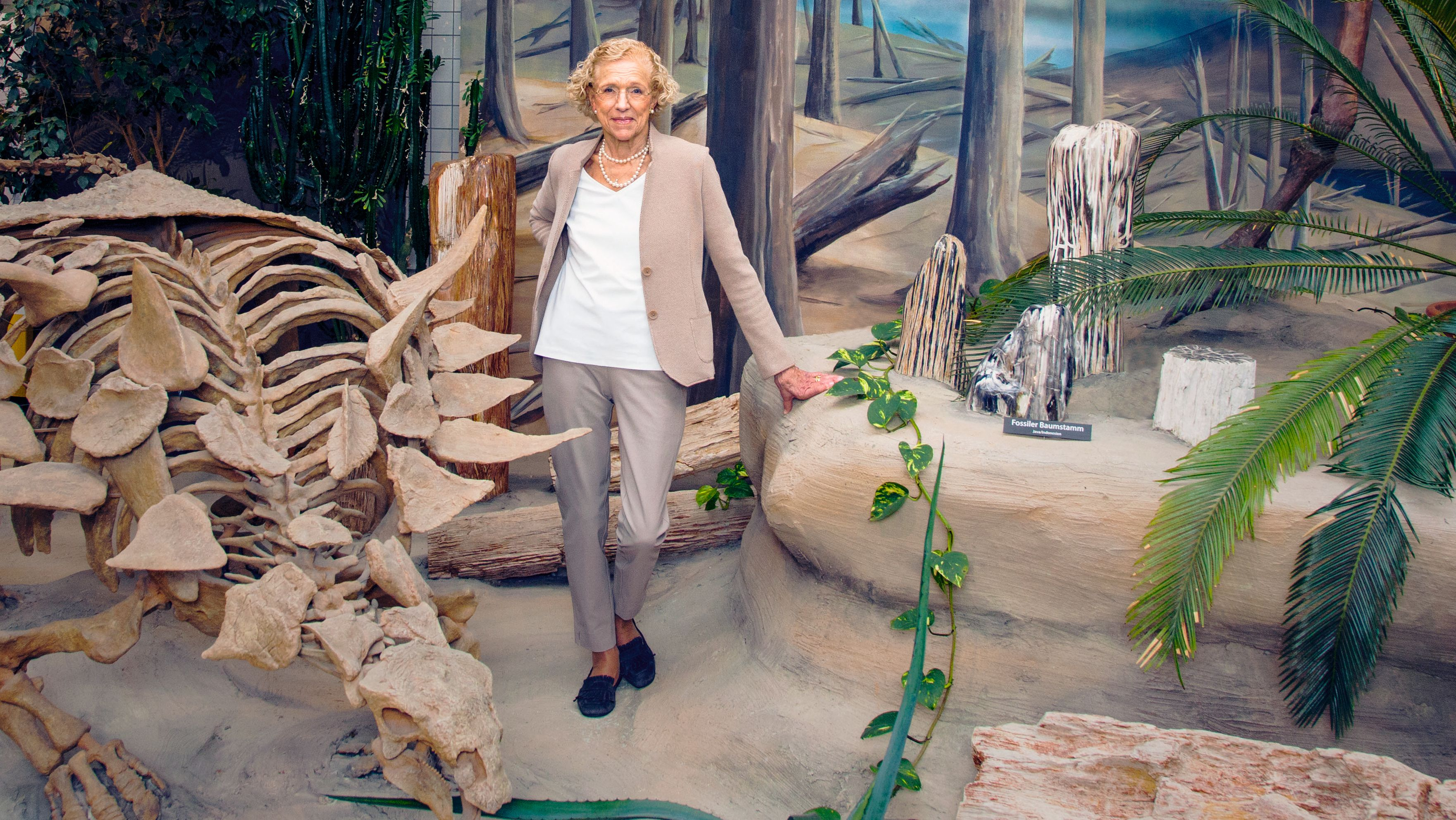 Eine ältere Frau steht neben einem Dinosaurierskelett.