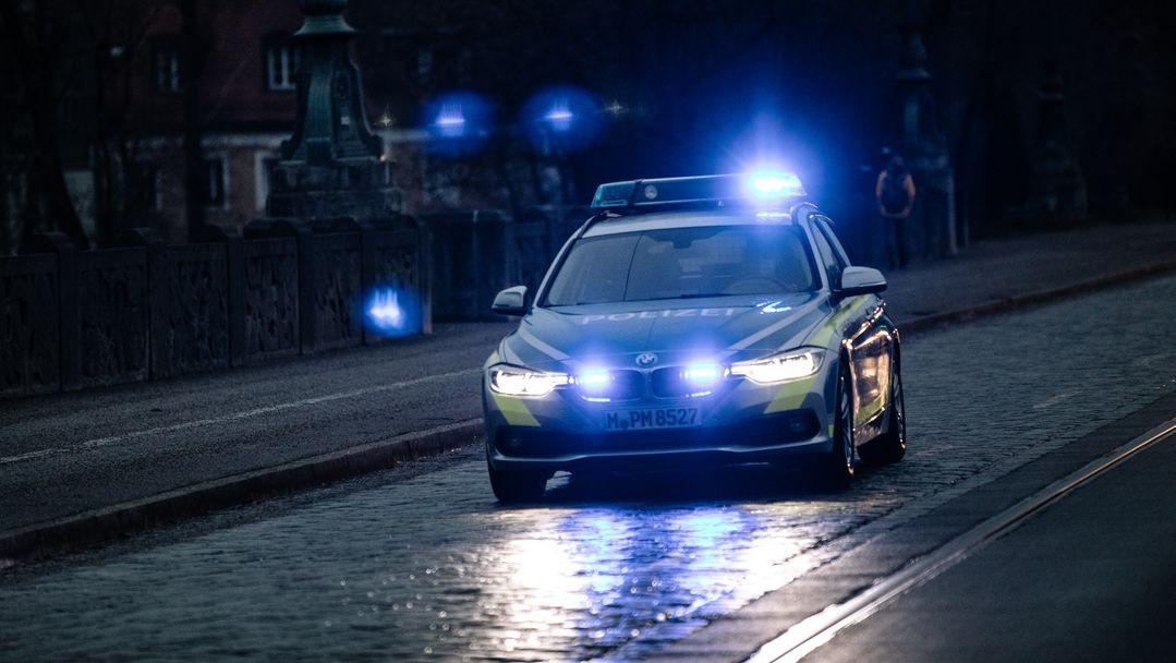 Ein Polizeiwagen mit Blaulicht fährt durch die Stadt (Symbolbild).