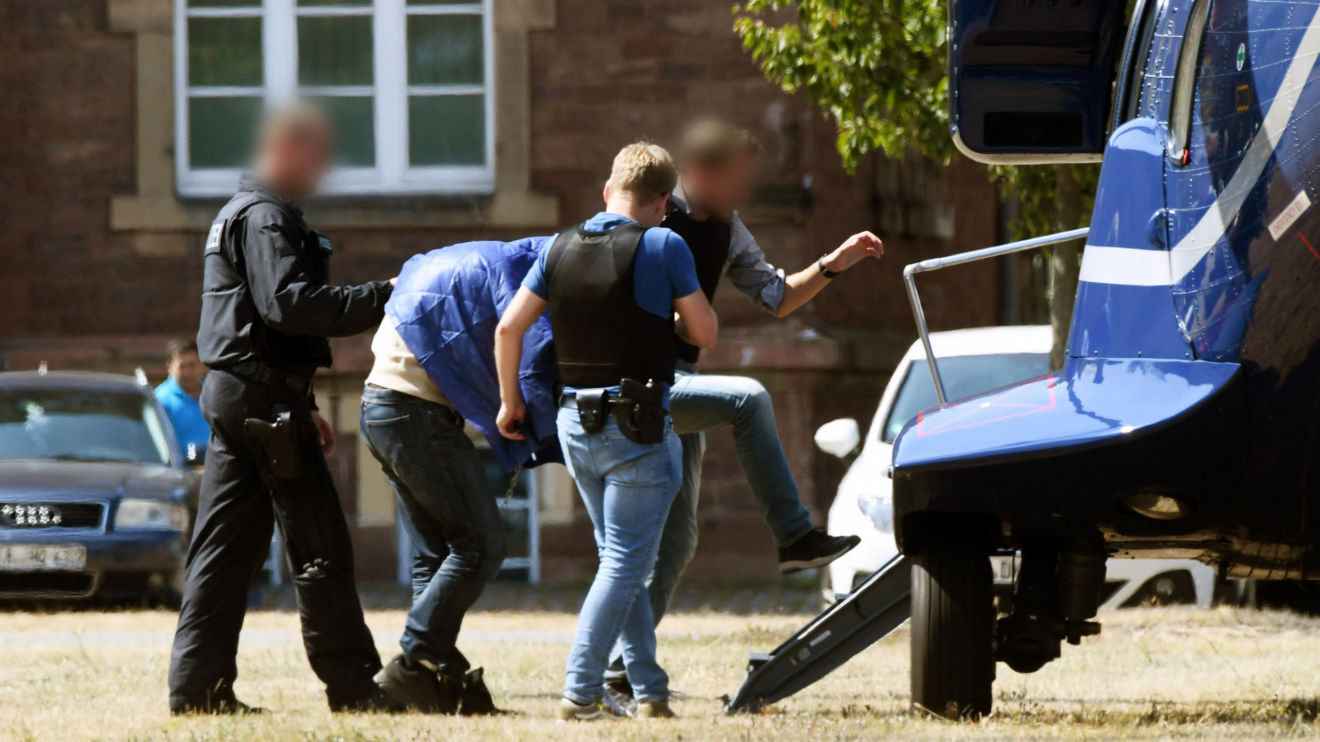 Der jetzt angeklagte Verdächtige wird von Polizisten zu einem Hubschrauber gebracht