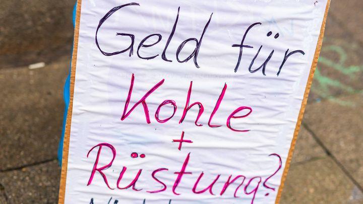 """Auf einem Plakat steht """"Geld für Kohle + Rüstung?"""""""