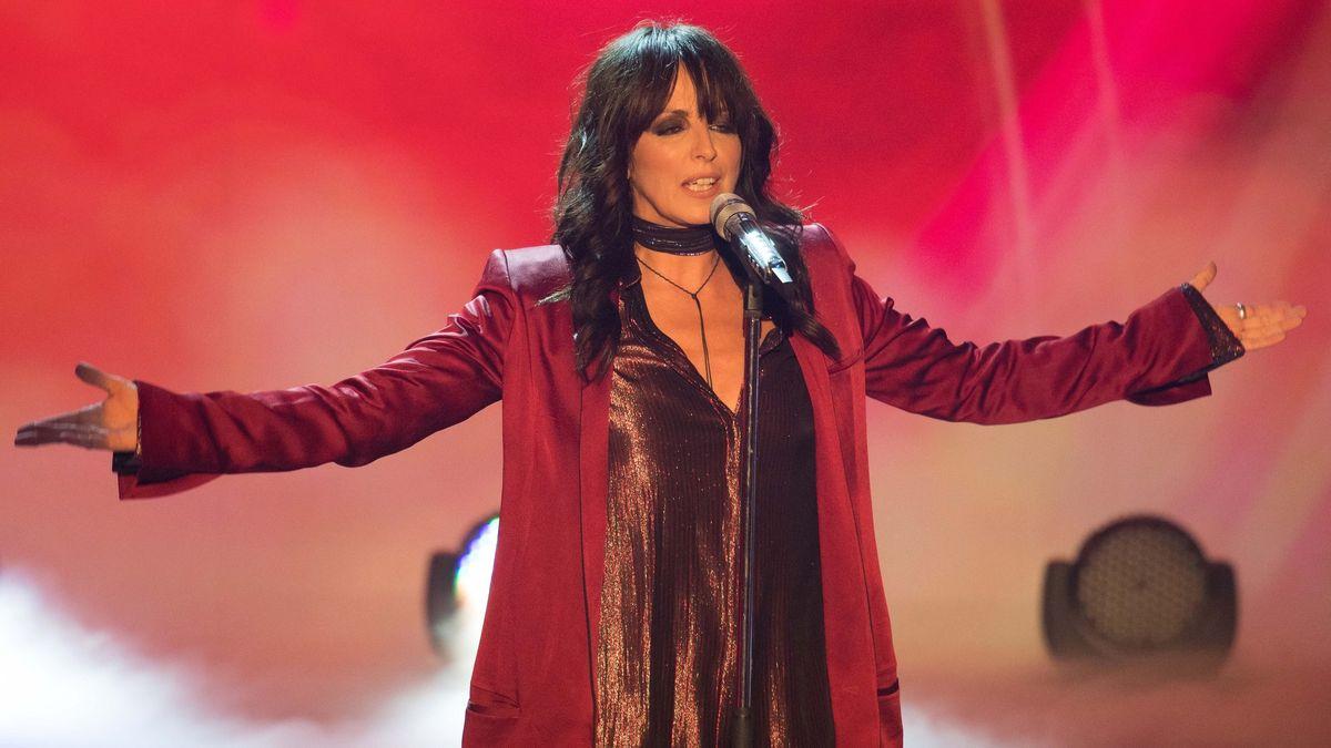 Sängerin Nena steht mit ausgebreiteten Armen im roten Mantel auf der Bühne