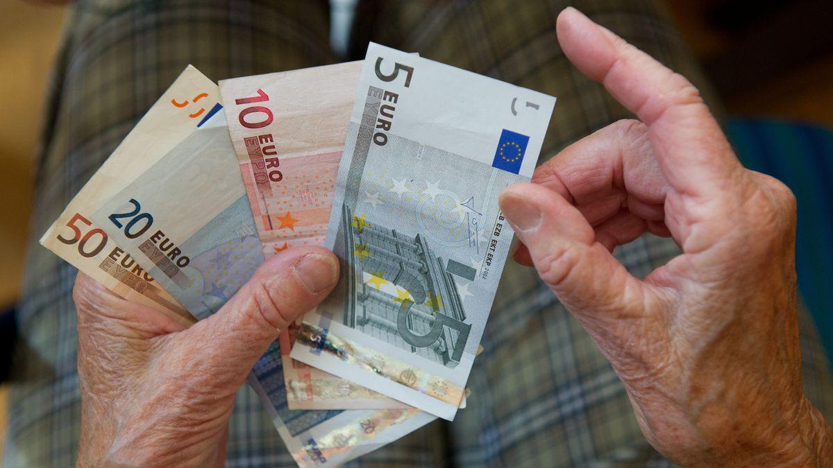Eine ältere Frau zählt Geldscheine
