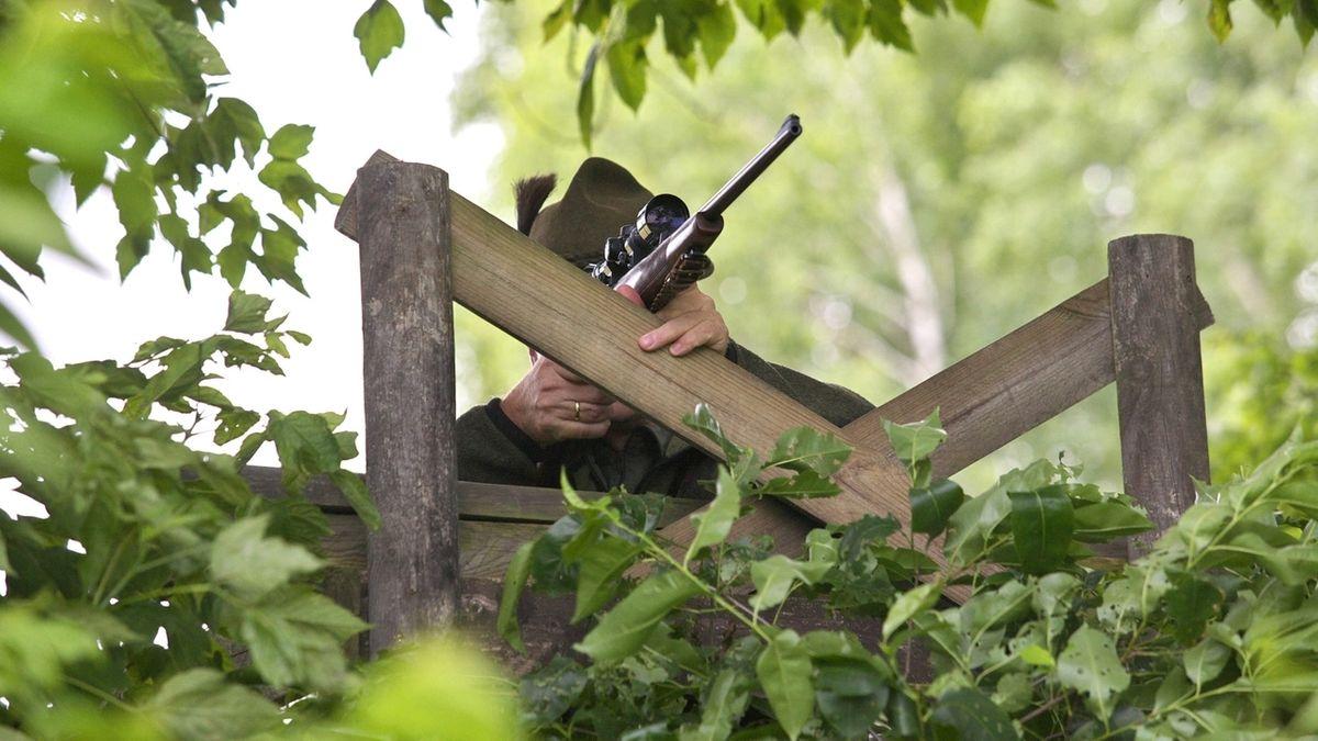 Jäger mit Jagdgewehr auf dem Hochsitz