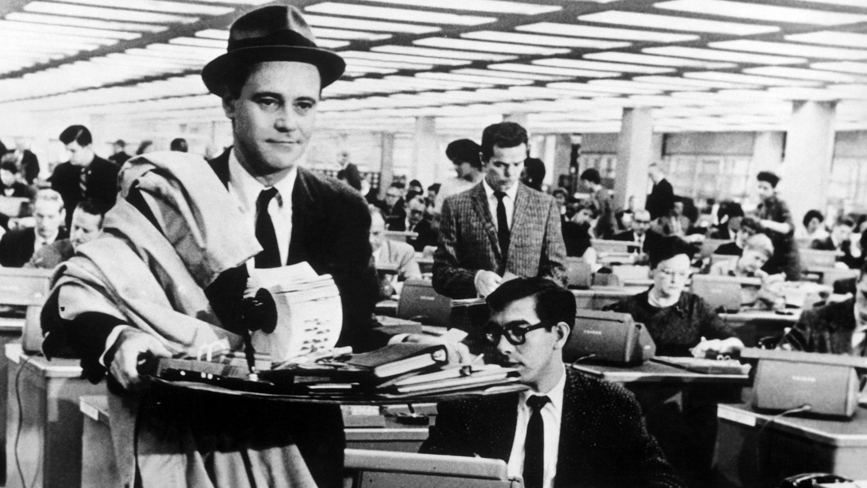 Ein Mann (JACK LEMMON) trägt in einem vollgestopften Großraumbüro seine Schreib-Untensilien durch die Gegend - auf der Suche nach einem Platz. Szene aus einer Komödie von Billy Wilder