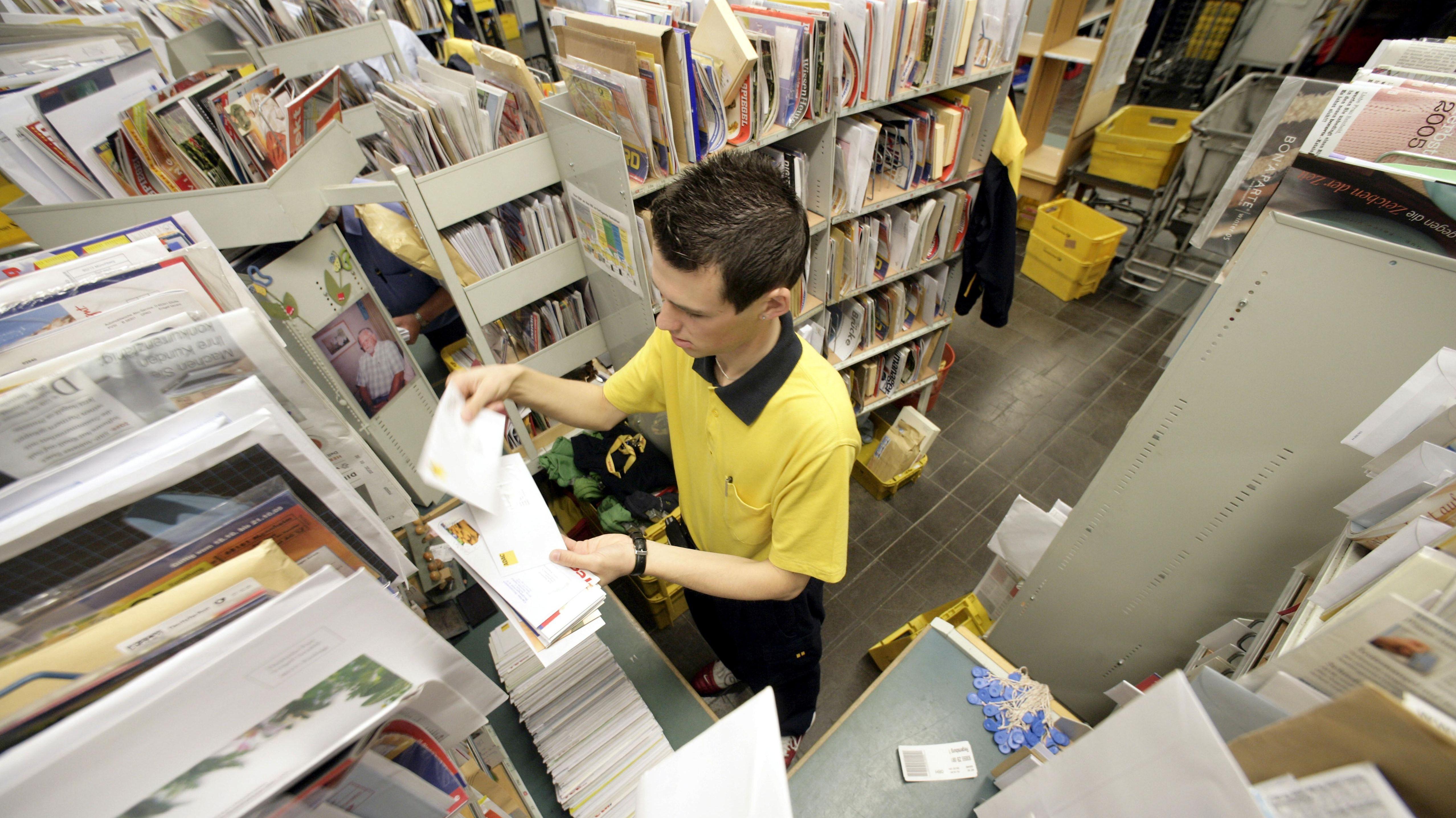 Ein Briefträger der Deutschen Post AG sortiert in seinem Zustellspind die Post im Zustellstützpunkt Regensburg.
