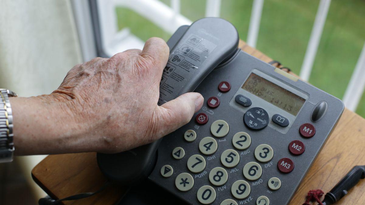 Hand eines Seniors auf einem Telefonhörer.