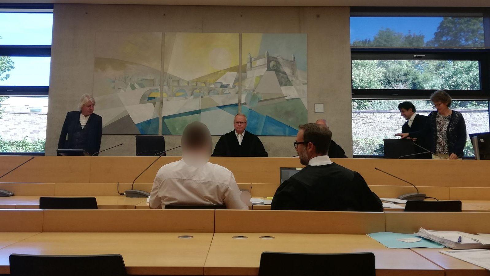 Mehrere Personen in einem Gerichtssaal.