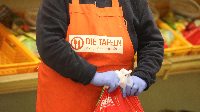 Eine Mitarbeiterin mit Latexhandschuhen verpackt Lebensmittel für Bedürftige in der Tafel