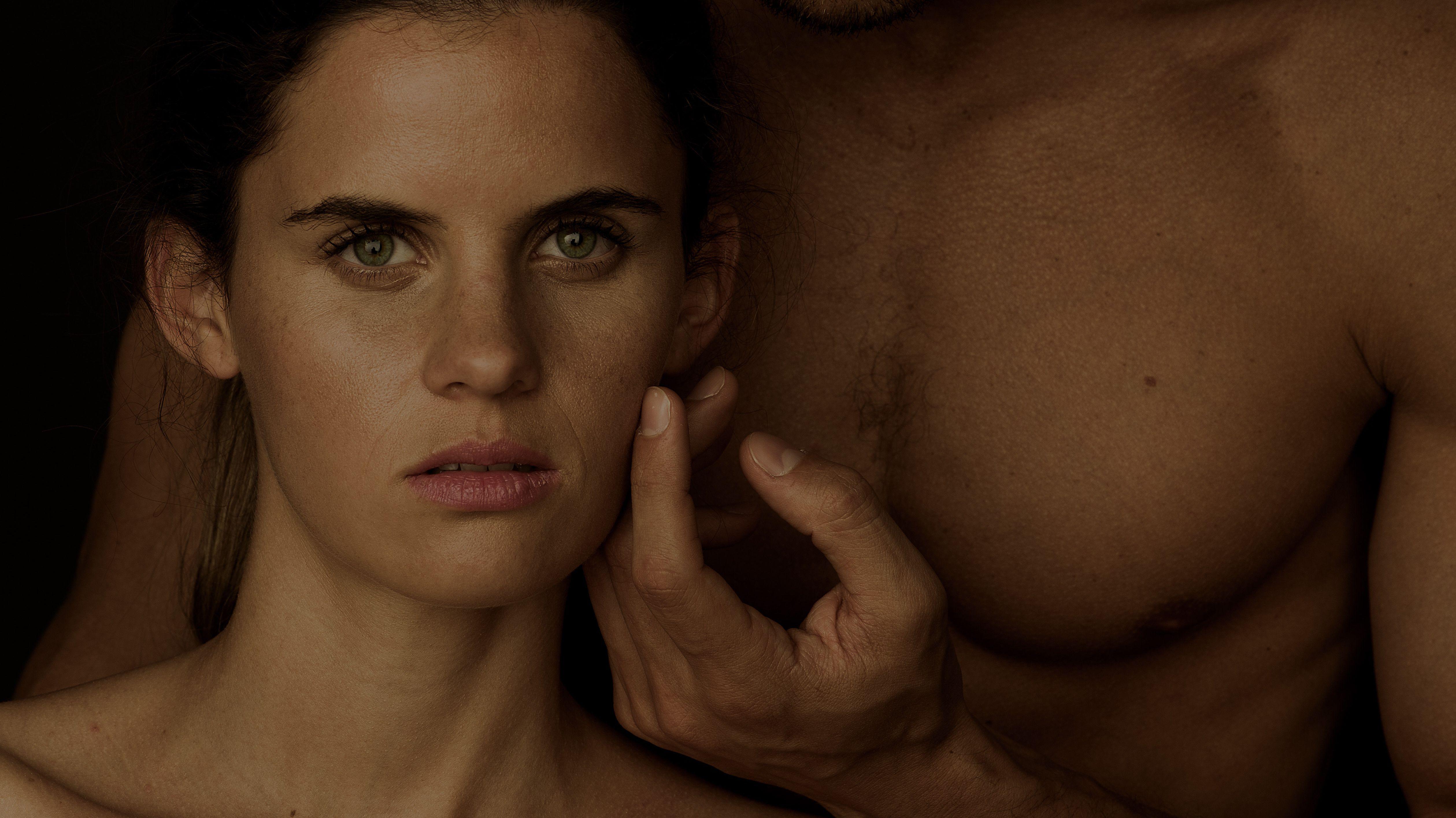 Eine Frau vor der nackten Brust eines Mannes