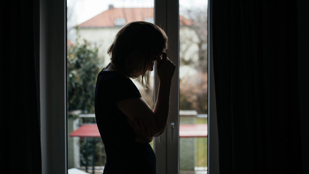 Frau steht vor Fenster und hält niedergeschlagen ihren Kopf in den Händen.