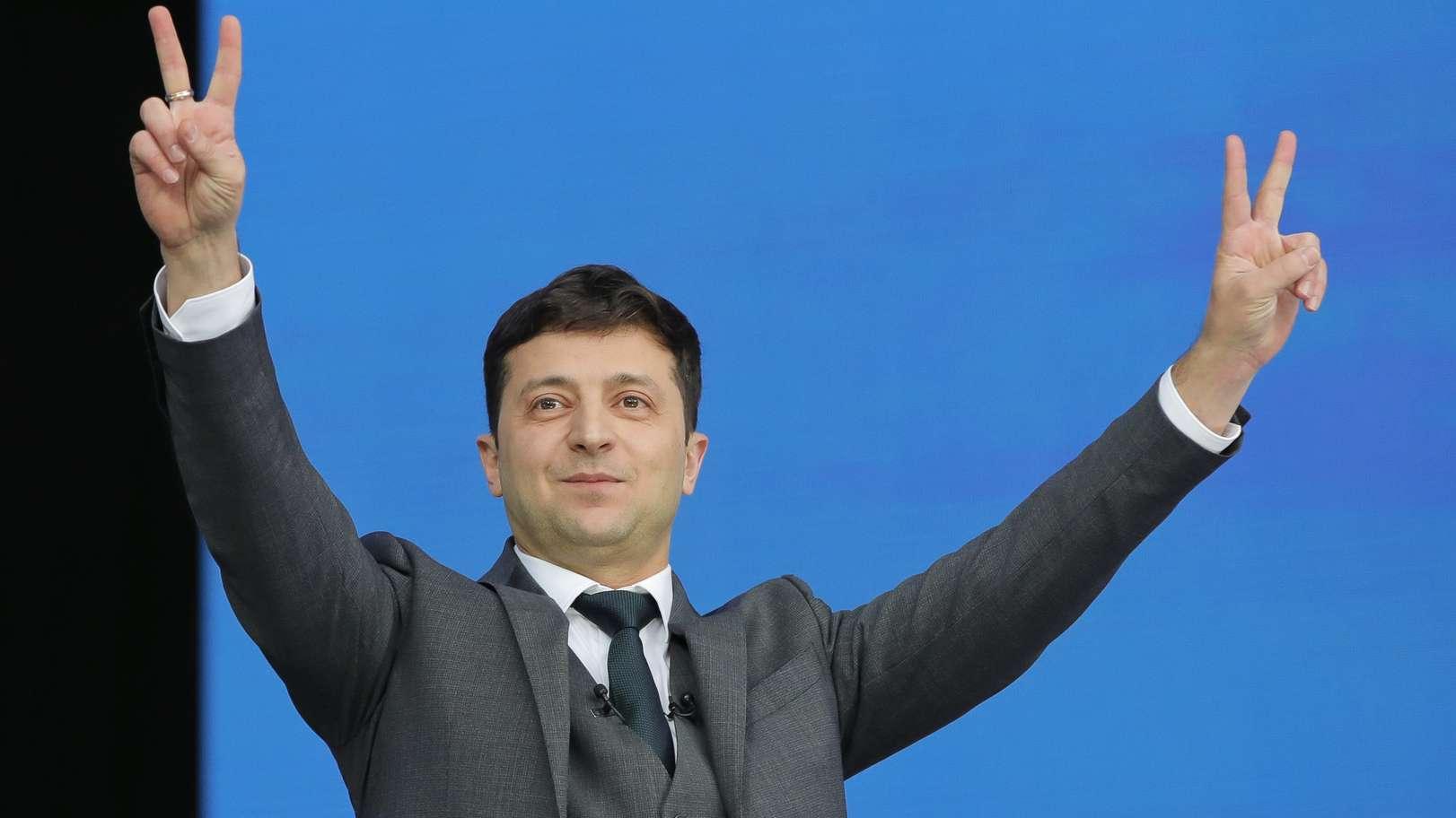 Wolodymyr Selenskyj macht mit beiden Händen das Victory-Zeichen.