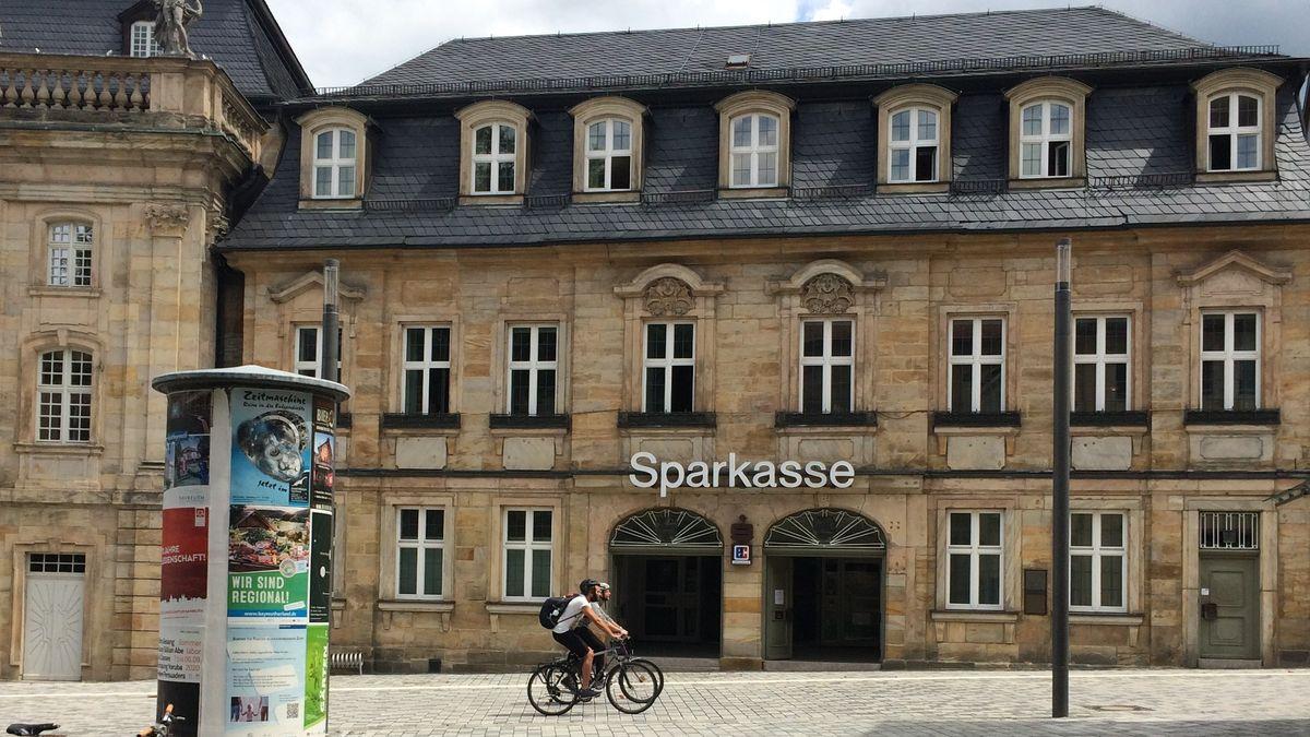 Die Sandsteinfassade des ehemaligen Sparkassen-Gebäudes in Bayreuth von der Straße aus gesehen, an dem zwei Radfahrer vorbeifahren.