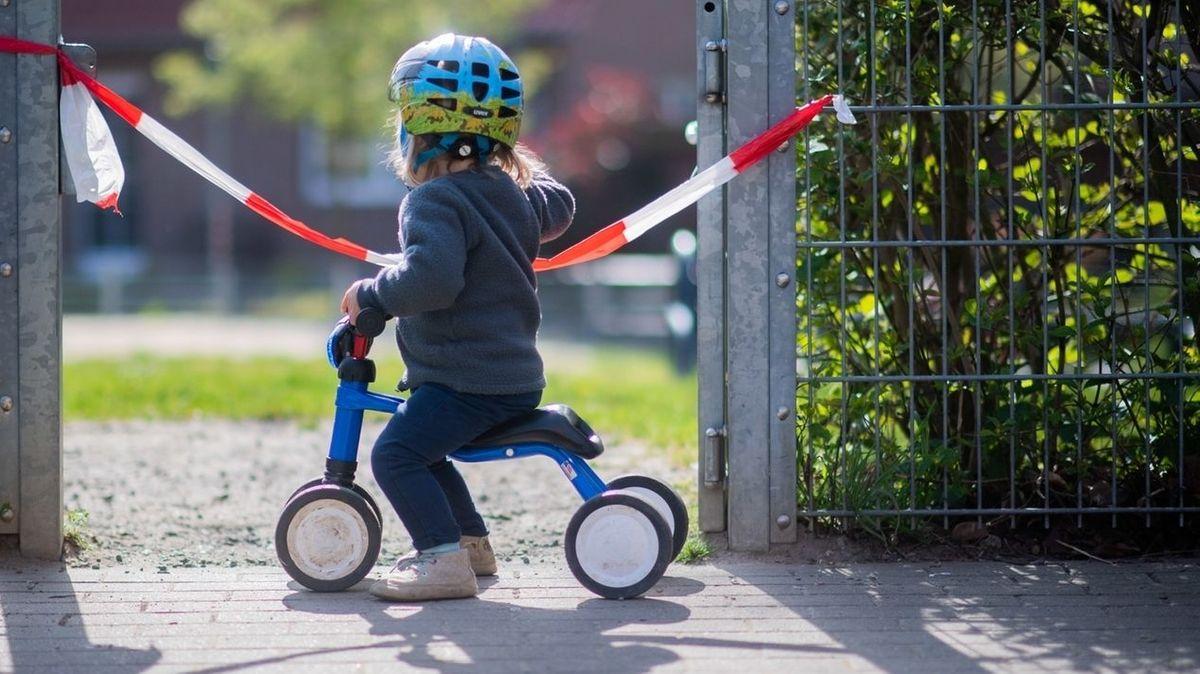 Ein Kind sitzt auf einem Dreirad vor einem Absperrband (Symbolbild)