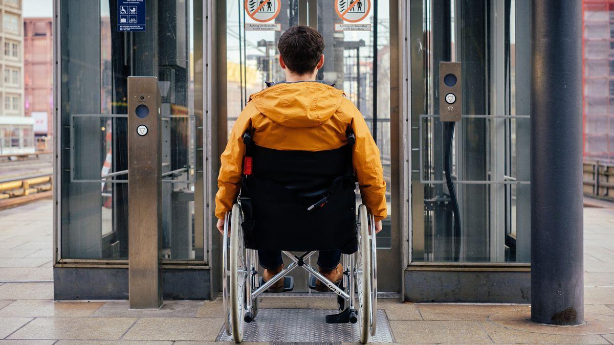 Ein Mann mit einem Rollstuhl vor einem Aufzug