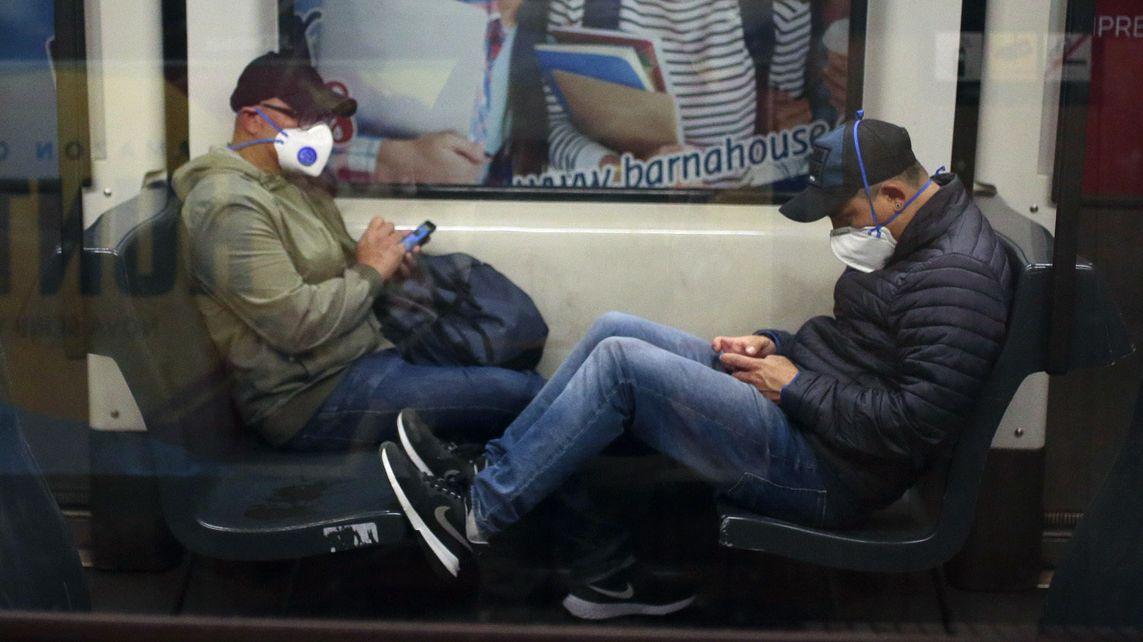 Zwei Passagiere mit Mundschutz sitzen in einem Zug und tippen auf ihren Handys.