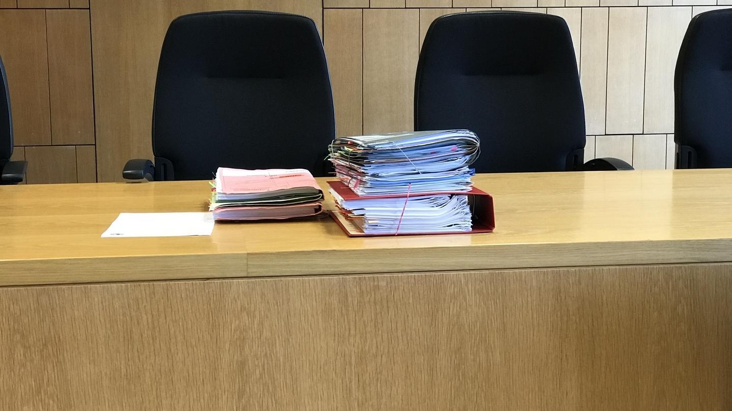Unterlagen liegen auf einem Tisch im Gerichtssaal