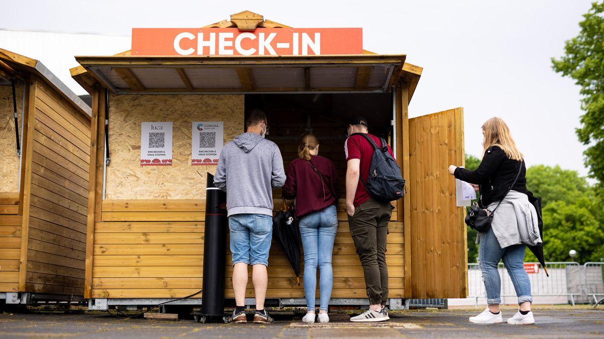 Besucher stehen am Einlass zur Gilde Parkbühne in Hannover und checken sich u.a. über die Corona-Warn-App für eine Veranstaltung ein (Symbolbild)