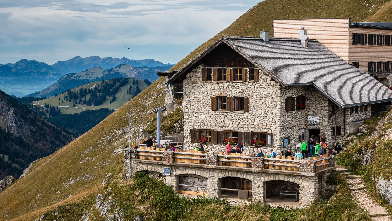 Die Bad Kissinger Hütte des Deutschen Alpenvereins ist gut besucht. Blick auf das steinerne Gebäude und die Terrasse, wo sich Wanderer aufhalten
