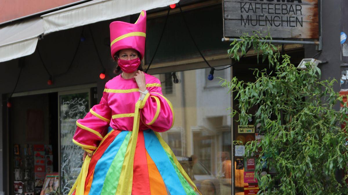 Ein bunter Clown tanzt auf Stelzen durch die Münchner Pestalozzistraße