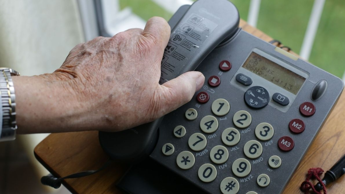 Hand eines Seniors greift zum Telefon