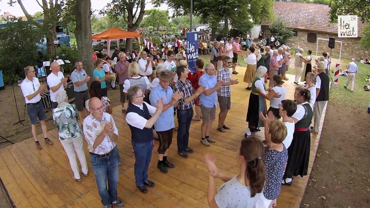 Beim Volksmusik-Picknick in Bergrheinfeld stehen Menschen auf einer Bühne und klatschen.