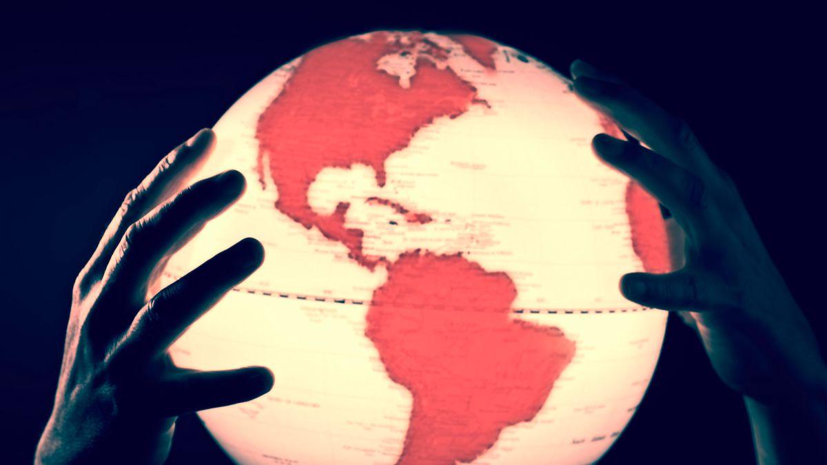 Hände halten einen Globus mit roten Kontinenten