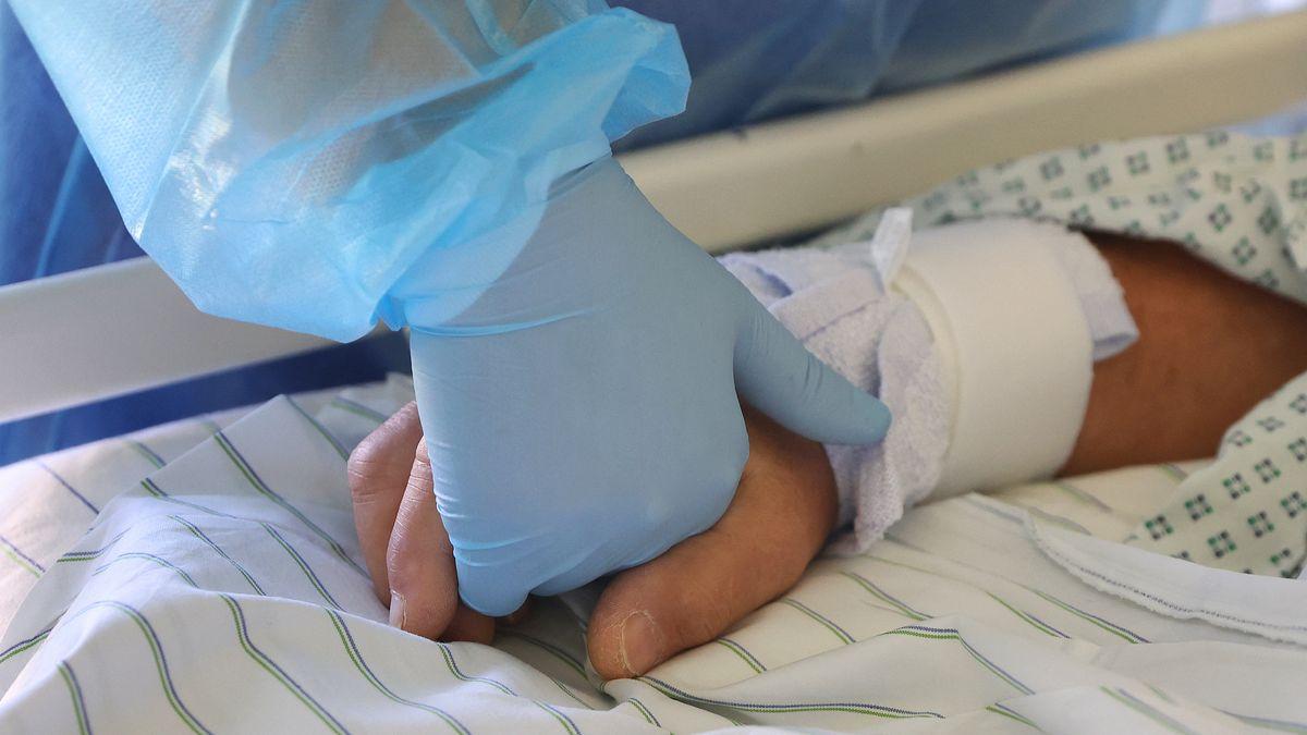 Ein Arzt hält die Hand eines Covid-19-Patienten im Klinikum Magdeburg.