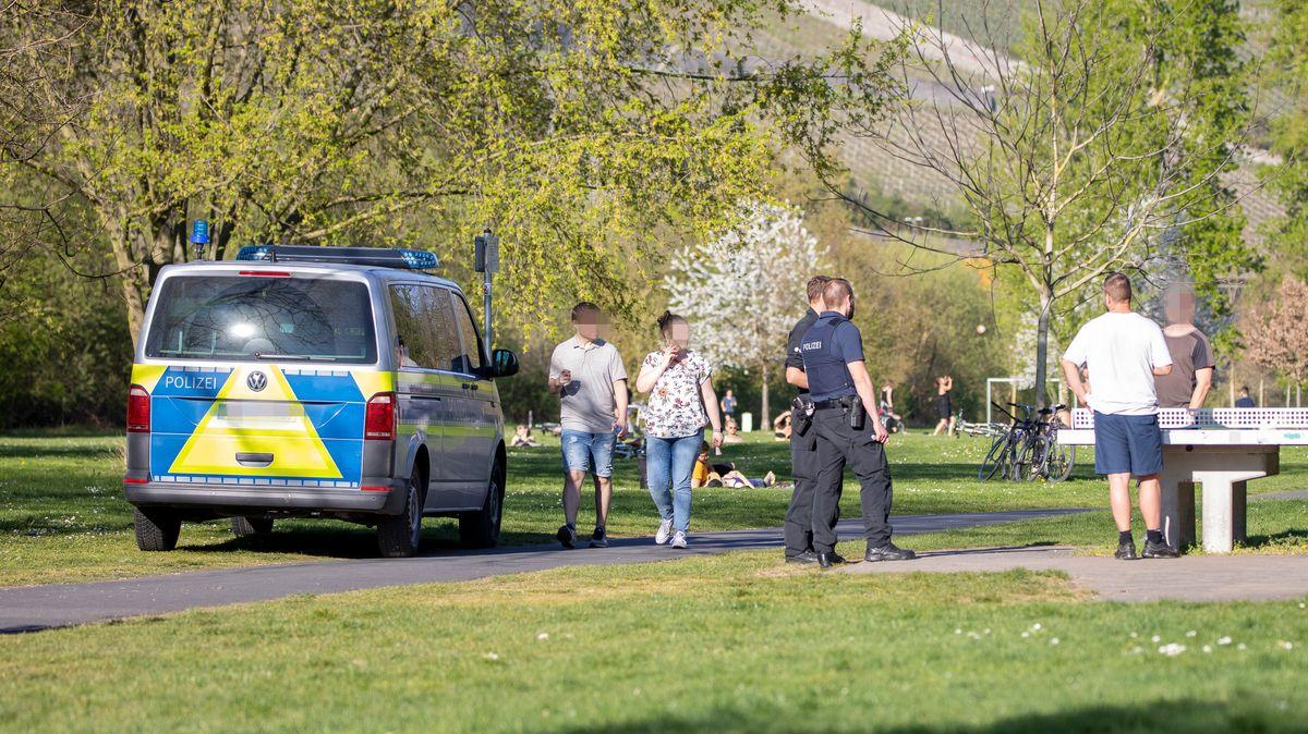 Polizeibeamte kontrolliert an den Würzburger Mainwiesen, ob die Bürger sich an die Ausgangsbeschränkungen halten