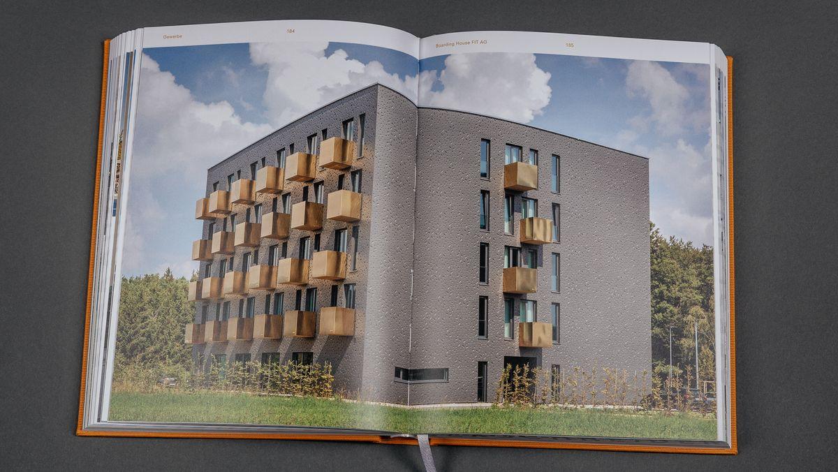 Das aufgeklappte gelbe Werkverzeichnis der Architekten  Berschneider +  Berschneider