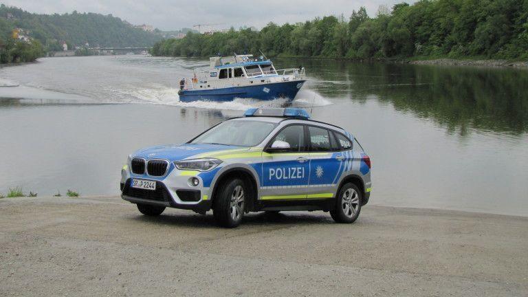 Ein Polizeiauto, dahinter ein Polizei-Schiff auf der Donau