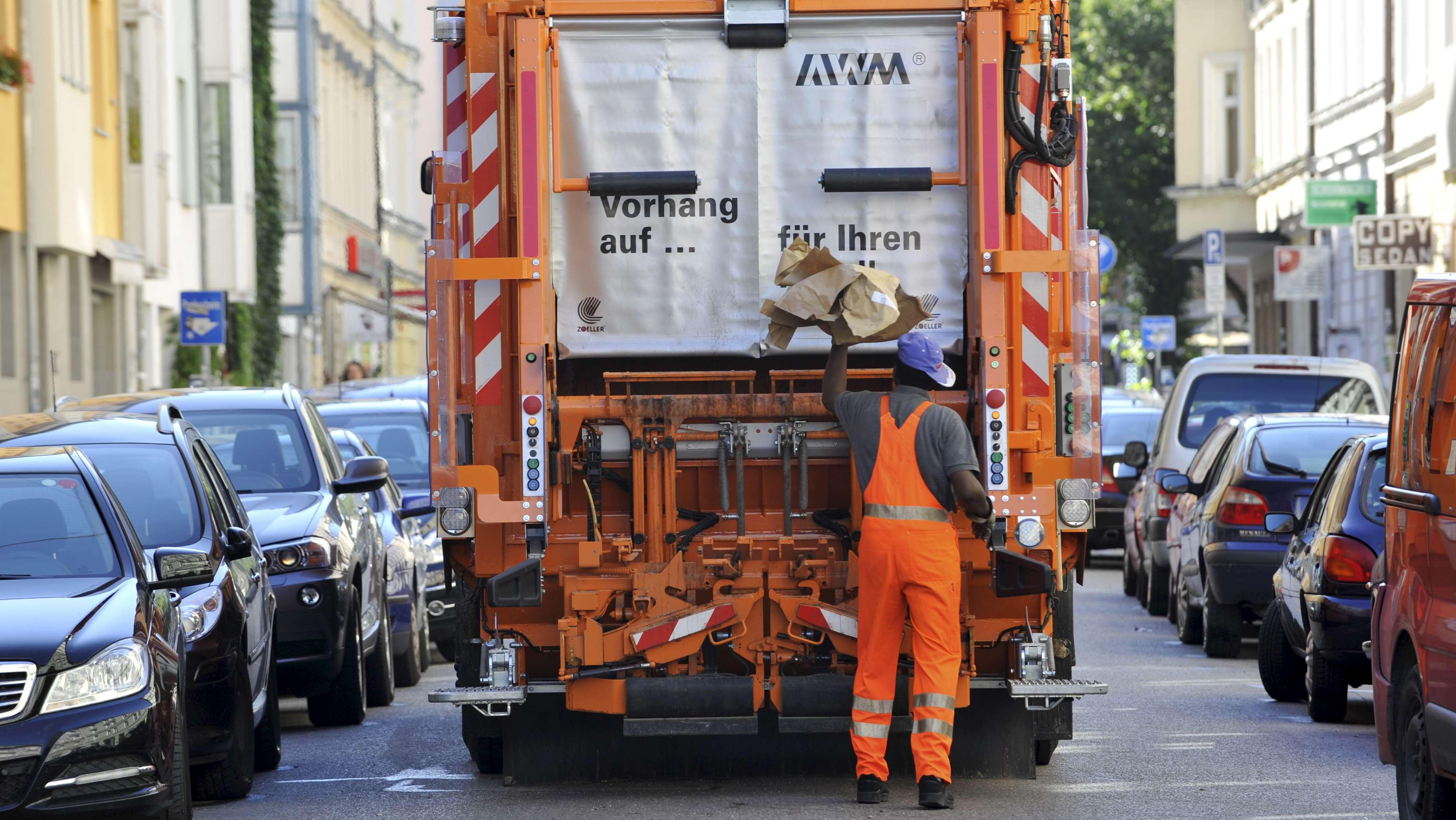 Müllwagen mit Müllmann bei der Müllentsorgung in München.