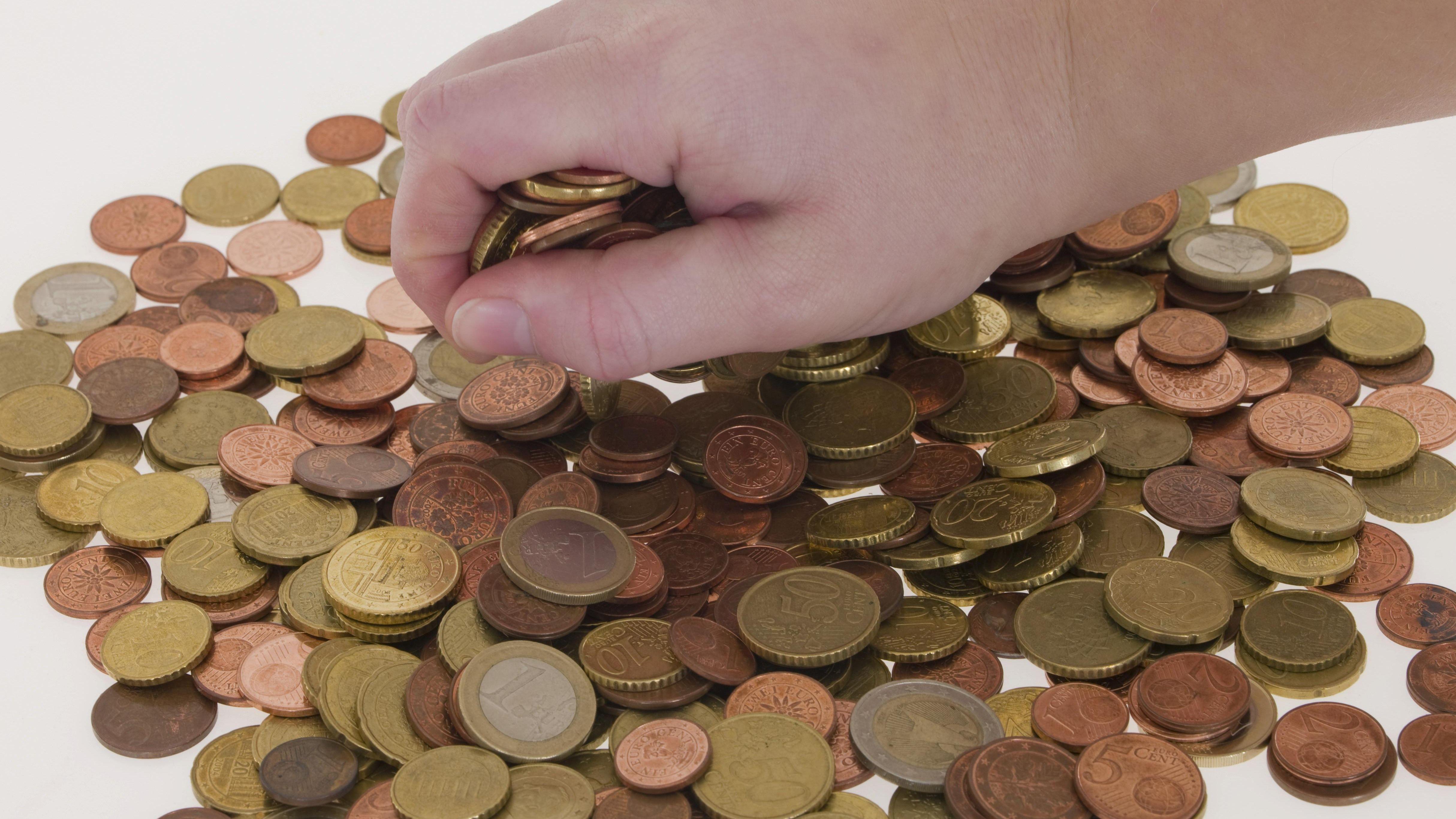 Hand greift in einen Haufen Münzgeld