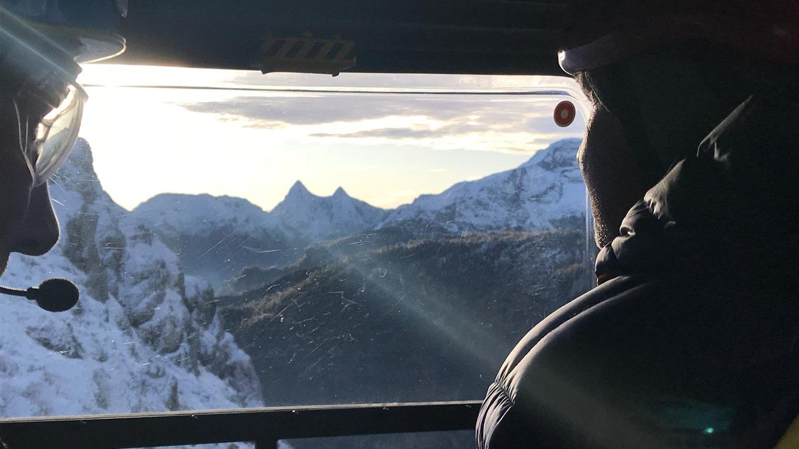 """Zwei Mitglieder der Bergwacht Ramsau im Rettungshubschrauber """"Christoph 14"""" über dem Steinernen Meer"""
