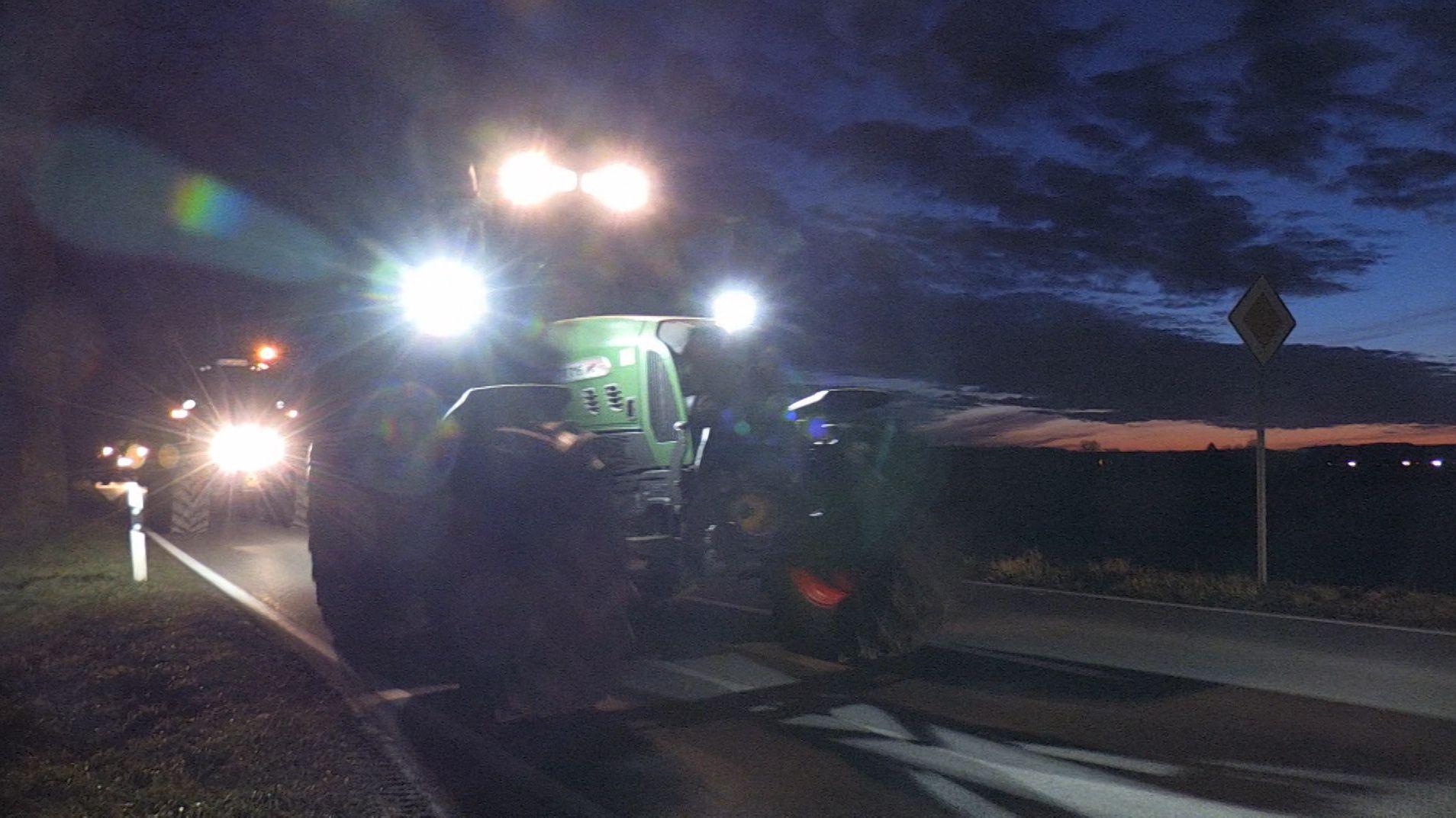 Traktoren eines Schlepper-Flashmobs nachts auf der Straße