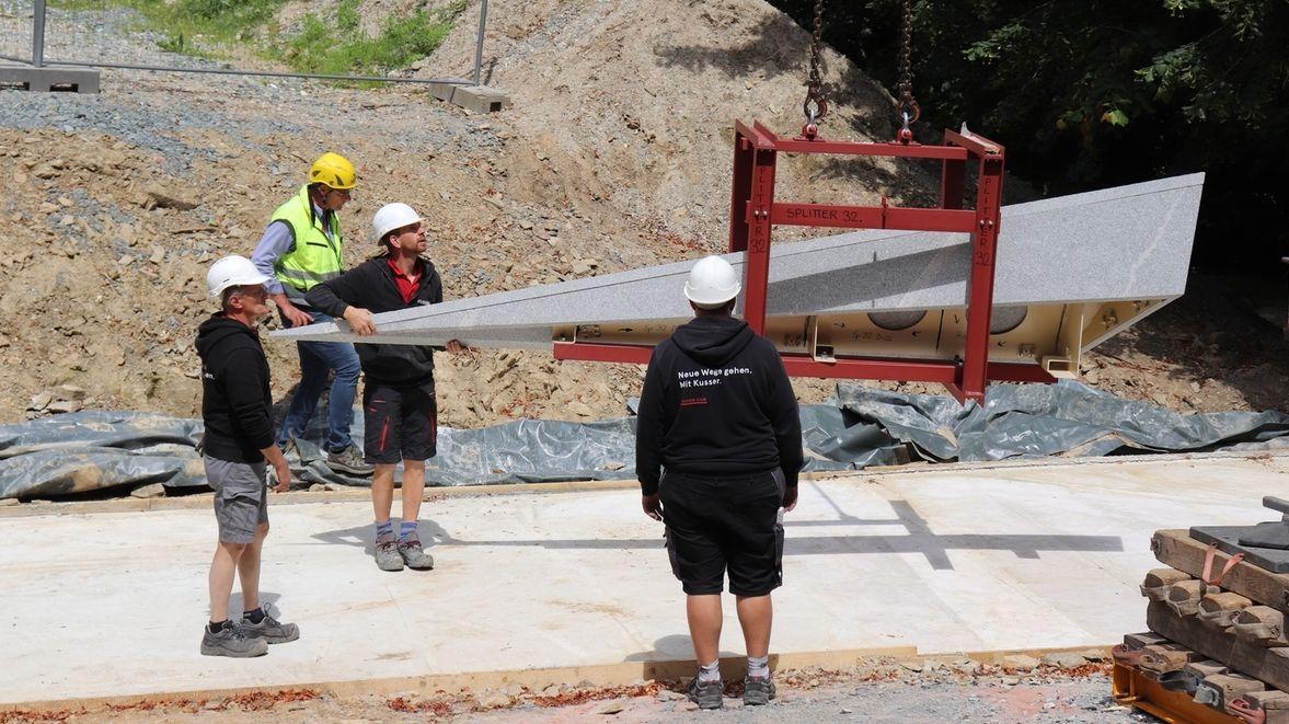 Arbeiter nehmen eine Granitspitze in Empfang, die an einem Kran hängt.