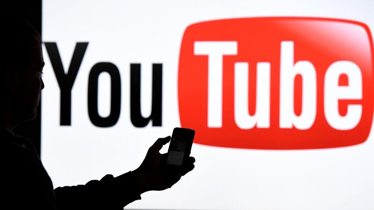 Eine Person, nur schattenhaft zu sehen, steht vor einer leinwand auf der das Logo von YouTube zu sehen ist und bedient ihr Handy.