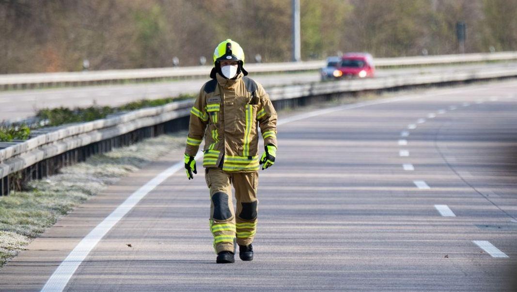 Ein Feuerwehrmann läuft nach einem Unfall über eine gesperrte Autobahn.