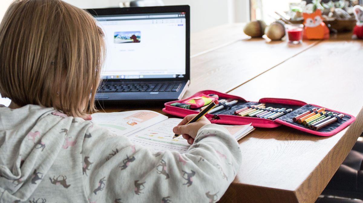 Kind mit einem Laptop beim Homeschooling