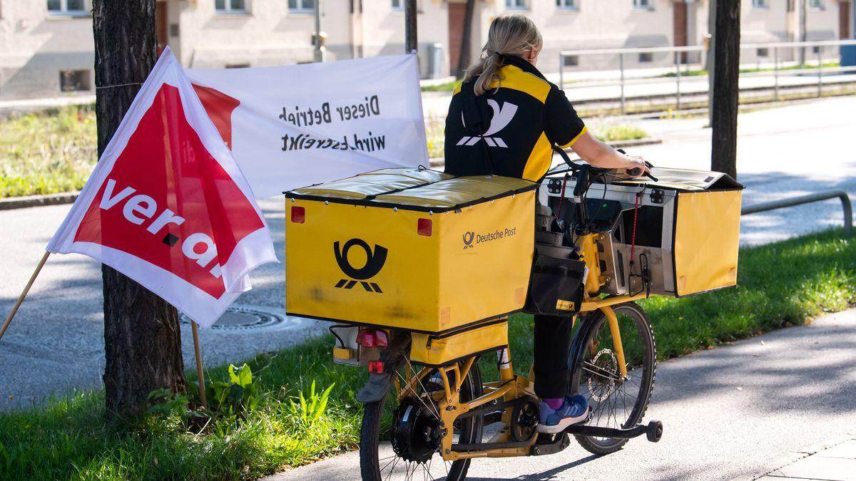 Postzustellerin vor einem Verdi-Plakat