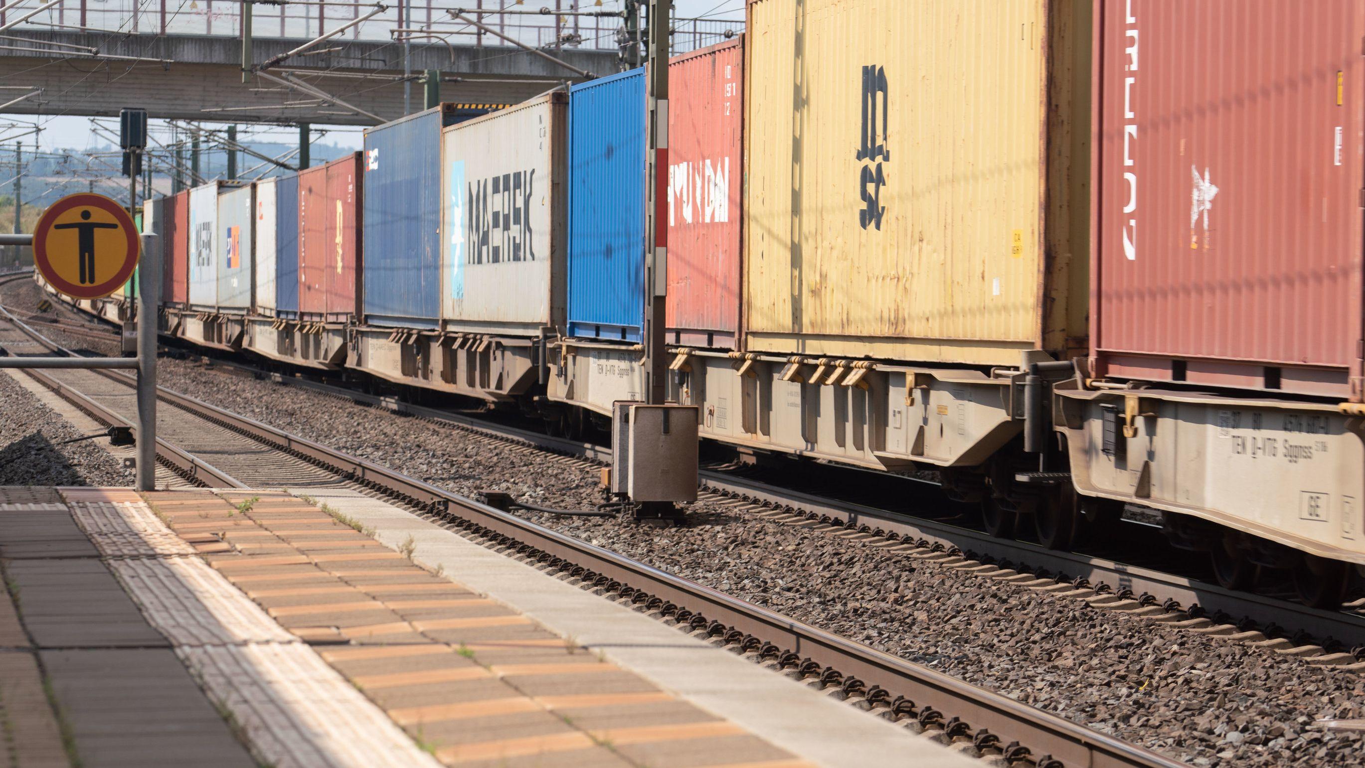 Ein Güterzug passiert einen Bahnsteig des Bahnhofs